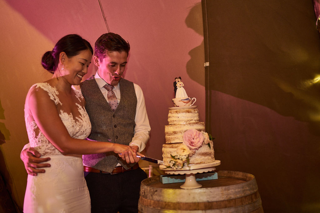 PapaKåta couple Lucy & Chris' Teepee Wedding in Terrington North Yorkshire captured by Chris Morse Photography- Cutting the cake
