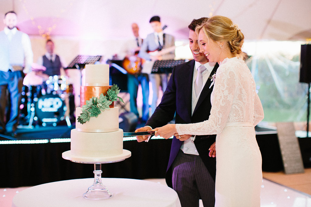 PapaKåta couple Georgina & Steve Sperry Tent Wedding in Barnby Dun, Doncaster captured by Melissa Beattie- Cutting the cake by Cherry Blossom Cakes