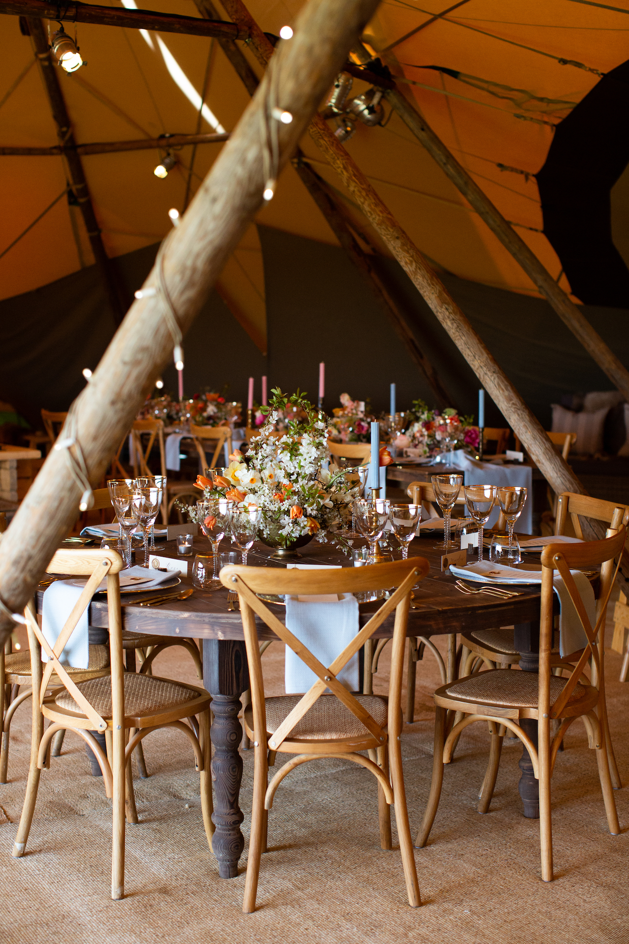 PapaKåta Spring Open Weekend Teepee captured by Lucy Davenport Photography: Round Farmhouse Table with Cross Back Chairs, Floral Centrepiece by Aelisabet Flowers
