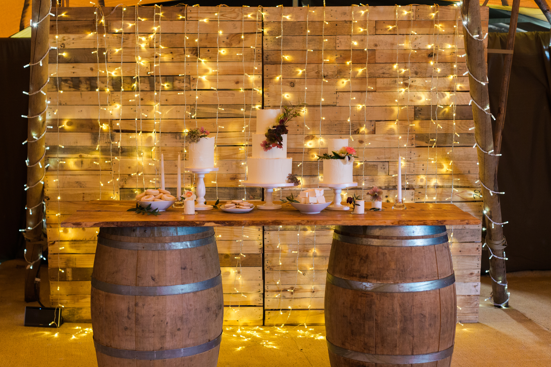 PapaKåta Spring Open Weekend Teepee captured by Lucy Davenport Photography: Wine Barrel Bar with Cake Display by Cherry Blossom Cakes, Fairy Light Baffle Backdrop